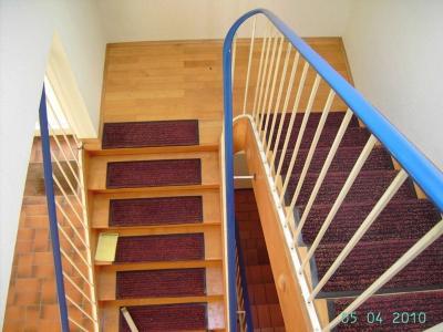 Die vorhandene Treppe mit Metallgeländer und Stufenschutz wurde renoviert. Ein durchlaufender Holzhandlauf mit Holz/Edelstahlstaketen ersetzen das alte Stahlgeländer, die verklebten Stufen und Wangen wurden abgeschliffen und natur lackiert.